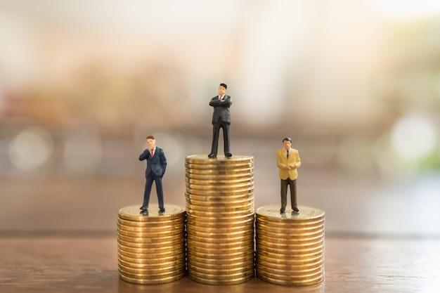 Affari, investimenti in denaro e concetto di pianificazione. chiuda su del gruppo di figura miniatura della gente dell'uomo d'affari che sta sulla pila di monete di oro sulla tavola di legno.