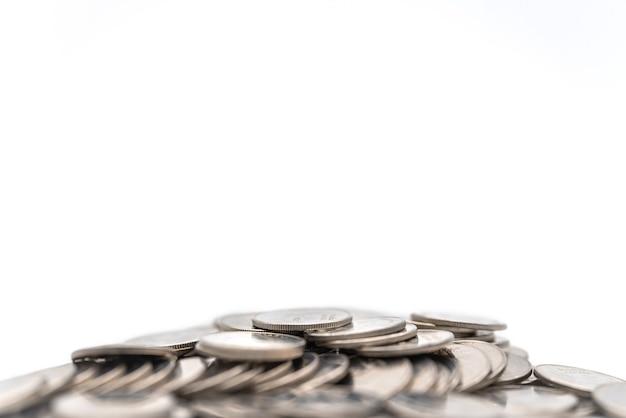 Affari, investimento di denaro e concetto di pianificazione. primo piano del mucchio di monete d'argento su sfondo bianco.