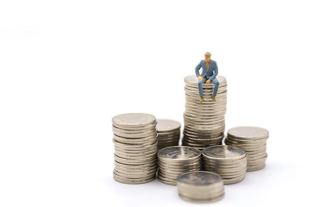 Affari, investimento di denaro e concetto di squadra. uomo d'affari in miniatura figura persone figura seduta in cima alla pila di monete d'argento su sfondo bianco.