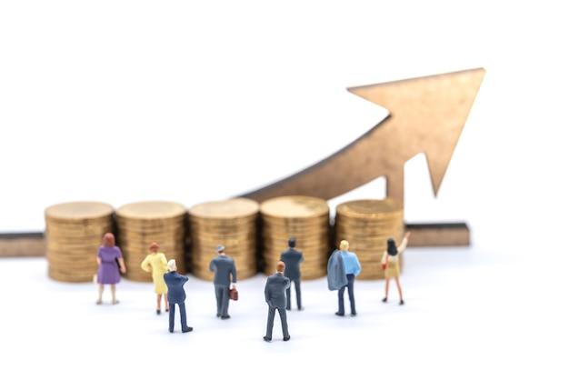 Concetto di affari, denaro e pianificazione. gruppo di imprenditore imprenditrice figura in miniatura persone in piedi e cercando di pila di monete d'oro con freccia in legno segno su sfondo bianco.