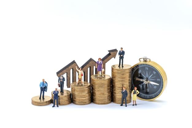 Concetto di affari, denaro e pianificazione. gruppo di uomo d'affari e donna d'affari figura in miniatura persone in piedi con pila di monete d'oro, segno di freccia in legno e bussola vintage su sfondo bianco.