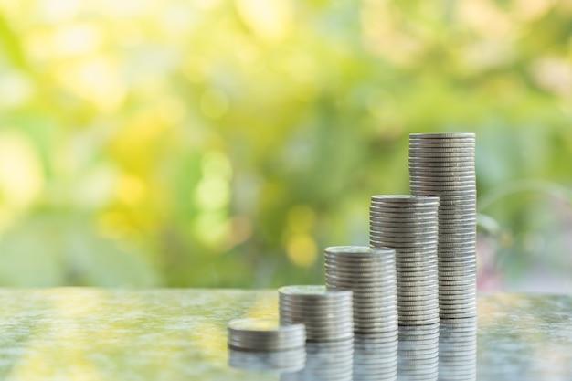 Concetto di affari, denaro, risparmio e sicurezza. chiuda su della pila di monete d'argento con bokeh del fondo verde della natura della foglia e copi lo spazio.