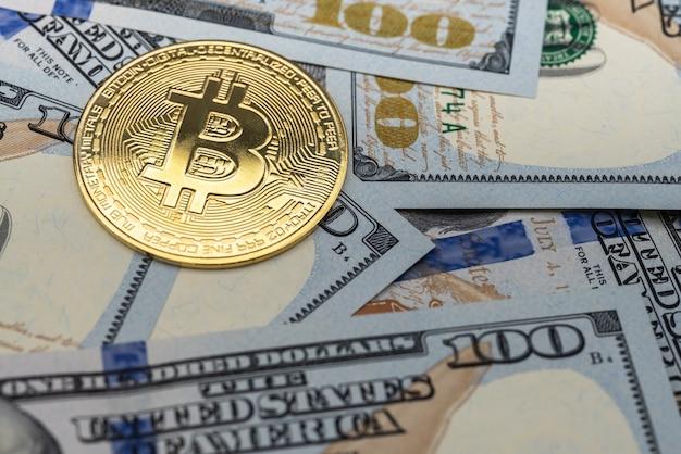 Concetto di affari, denaro, tecnologia e criptovaluta. primo piano della moneta bitcoin oro su una pila di 100 banconote in dollari usa.