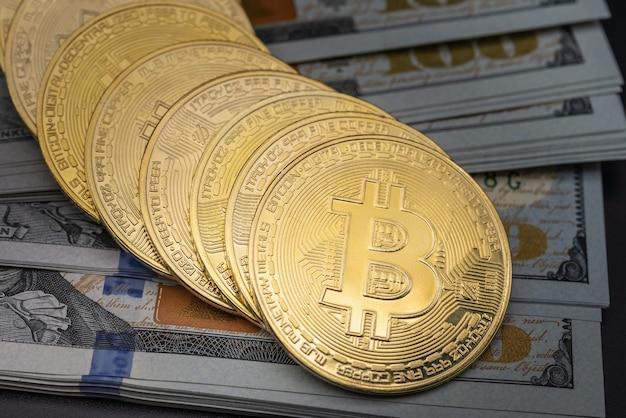 Concetto di affari, denaro, tecnologia e criptovaluta. primo piano delle monete bitcoin oro su una pila di 100 banconote in dollari usa.
