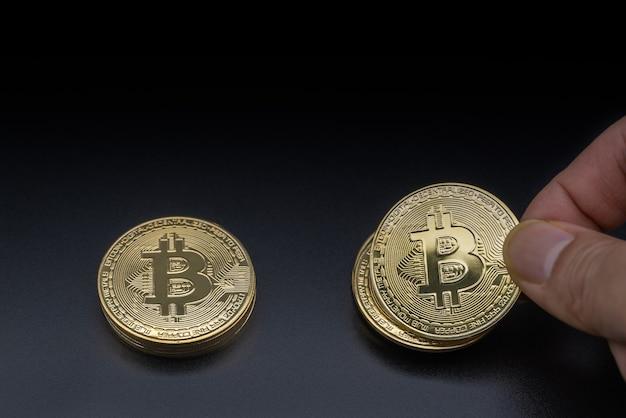 Concetto di affari, denaro, tecnologia e criptovaluta. primo piano della mano dell'uomo che tiene un bitcoin oro monete in cima alla pila di monete su sfondo nero.
