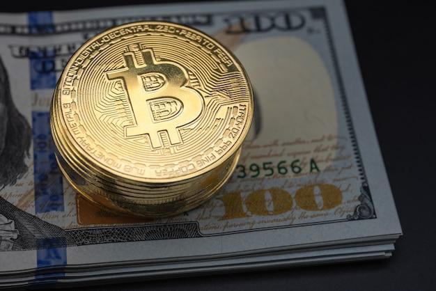 Concetto di affari, denaro, tecnologia e criptovaluta. primo piano della pila di monete d'oro bitcoin sulla pila di 100 banconote in dollari usa.