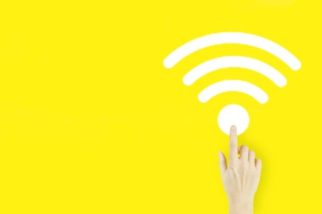 Concetto di connessione di rete aziendale. il dito della mano della giovane donna che indica con l'ologramma wi-fi su fondo giallo. concetto senza fili wi-fi.
