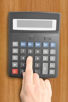 Oggetti aziendali. calcolatrice elettronica con una mano