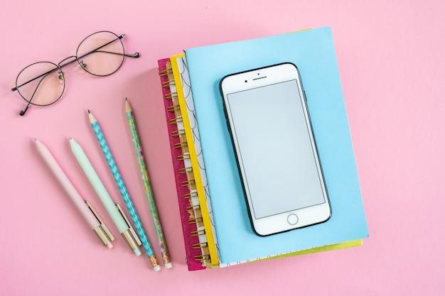 Oggetti aziendali per la pianificazione del lavoro, smartphone e occhiali da vista del manager sul tavolo o sullo sfondo rosa