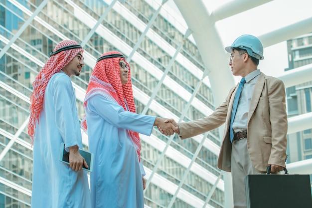 Concetto di affari e ufficio - arabo e uomo d'affari si stringono la mano sullo sfondo del paesaggio urbano