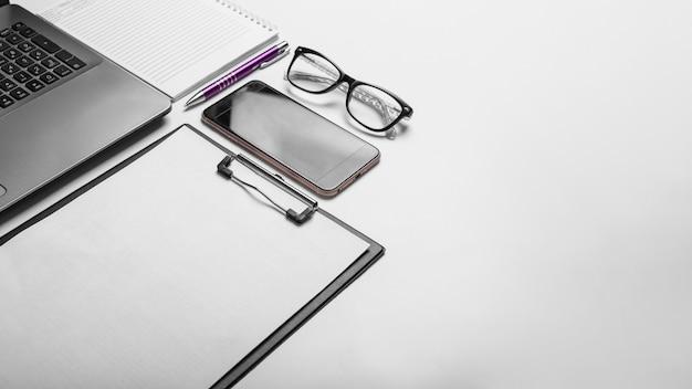 Business e concetto di ufficio con laptop e smartphone su sfondo bianco con spazio di copia