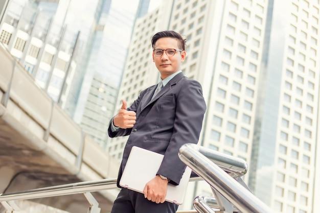 Affari e concetto di ufficio. buisnessman bello della giovane asia che mostra i pollici su.