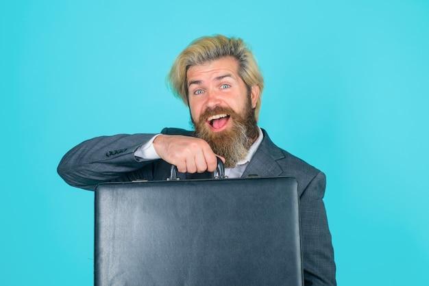 Uomo d'affari sorridente dell'impiegato di ufficio di affari con l'uomo d'affari barbuto dell'amministratore delegato della valigia in affari del vestito