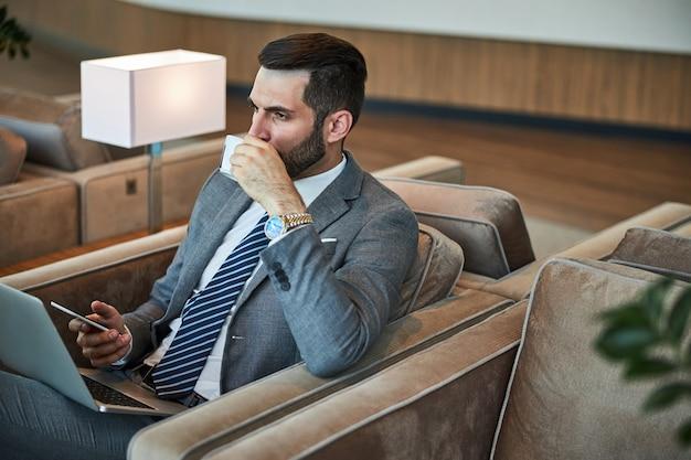 Funzionario aziendale che beve un caffè in una sala d'attesa