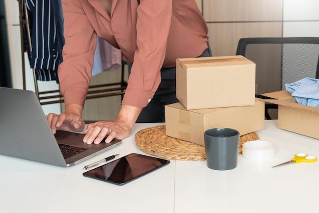 L'imprenditore che lavora a casa con la scatola di imballaggio del suo negozio online si prepara a consegnare i prodotti