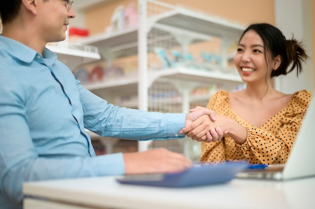 Gli imprenditori stanno analizzando i dati aziendali, parlando e sorridendo in un negozio moderno