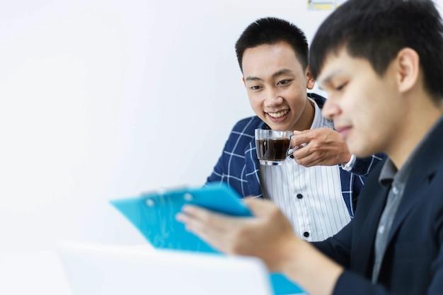 Concetto di partner commerciali due giovani imprenditori maschi che si divertono con un caffè gustoso mentre fanno brainstorming di idee per creare il concetto di un nuovo progetto.