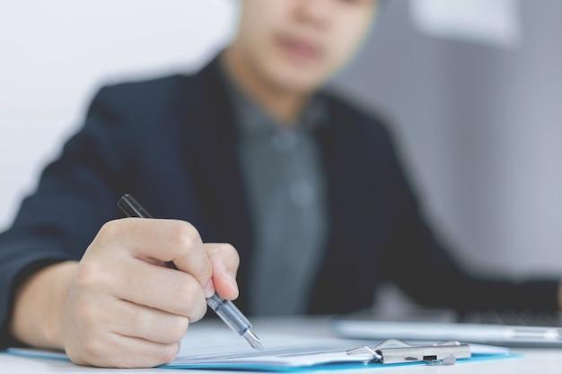 I partner commerciali concepiscono un giovane uomo d'affari in possesso di una penna che punta al riepilogo dei profitti dell'ultimo mese mostrato nei moduli dei documenti.