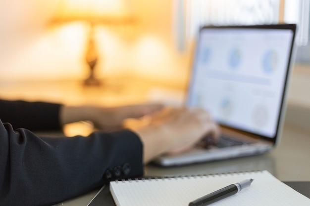 I partner commerciali concepiscono un giovane uomo d'affari che utilizza un computer portatile che rivede il riepilogo delle vendite annuali.