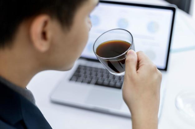 I partner commerciali concepiscono un giovane imprenditore maschio che tiene una tazza di caffè nero seduto con un laptop mentre partecipa a una riunione mensile.
