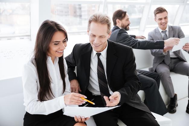 I partner commerciali discutono di qualcosa e si siedono sul divano in ufficio