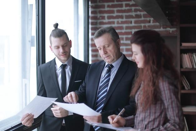 Partner commerciali che discutono di documenti aziendali in piedi in ufficio