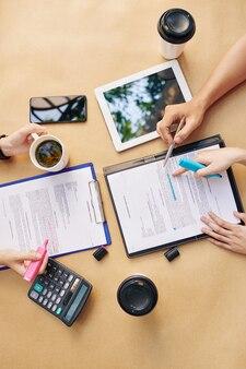 Partner commerciali che discutono i termini del contratto durante la riunione ed evidenziano le parti importanti