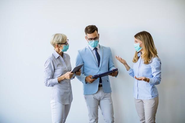 I soci commerciali che stanno e che esaminano i risultati di affari in ufficio mentre indossano le maschere di protezione come protezione da virus