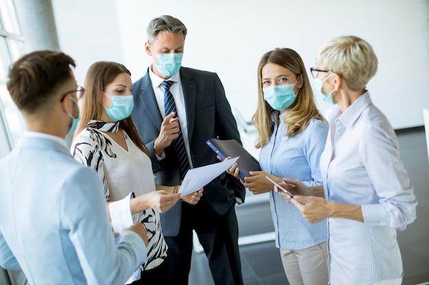 I partner commerciali in piedi e guardando i risultati aziendali in ufficio indossando maschere per il viso sono una protezione antivirus