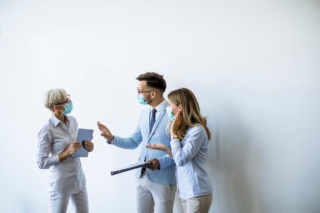 I partner commerciali in piedi e guardando i risultati aziendali in ufficio mentre indossano maschere per la protezione da virus
