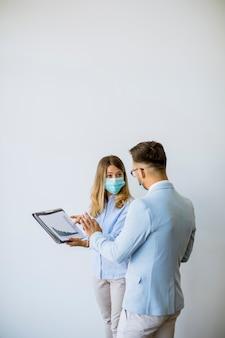 I partner commerciali in piedi e guardando i risultati aziendali in ufficio mentre indossano maschere per il viso sono una protezione antivirus
