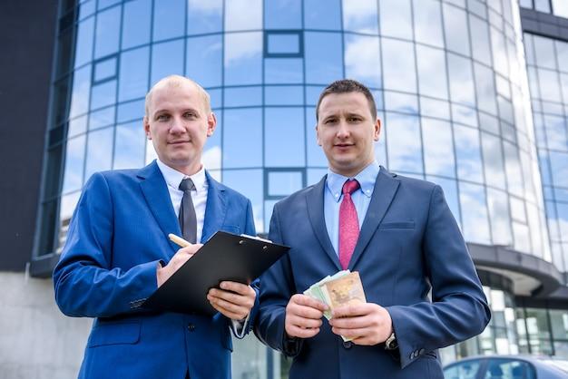Partner commerciali in giacca e cravatta che fanno affari in piedi all'aperto