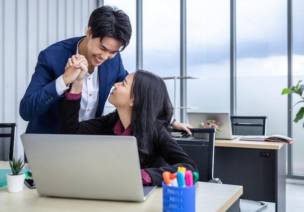 I partner commerciali maschiaccio lesbica e donna d'affari che lavorano sorridendo felice e sicuro di un business plan di successo sul computer portatile. lavorare insieme con il sorriso sulla mano in ufficio