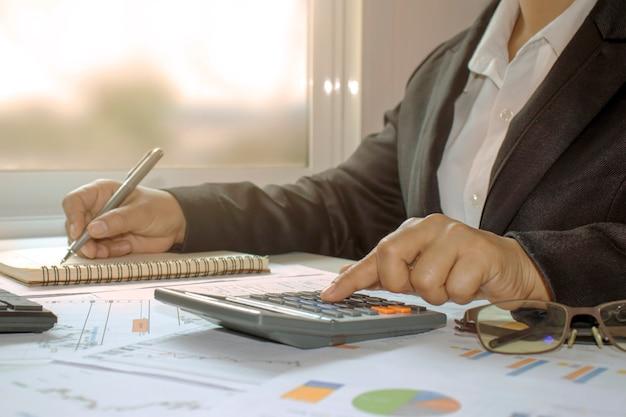 Gli uomini d'affari calcolano il reddito e il profitto degli investimenti, le idee per i budget degli investimenti e il risparmio di denaro nelle recessioni economiche.