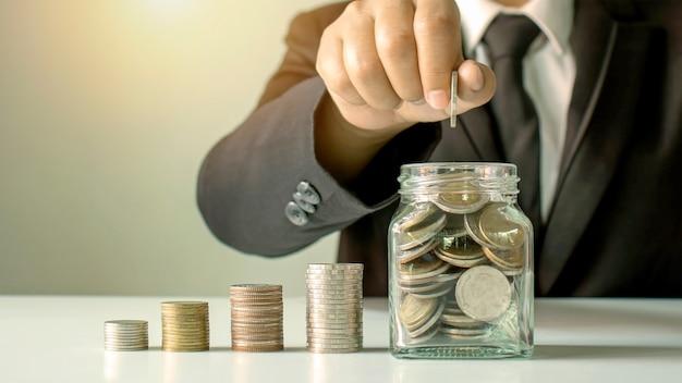 Gli uomini d'affari tengono denaro in una bottiglia di denaro per risparmiare denaro per idee di investimento, risparmio di denaro e investimenti sostenibili.
