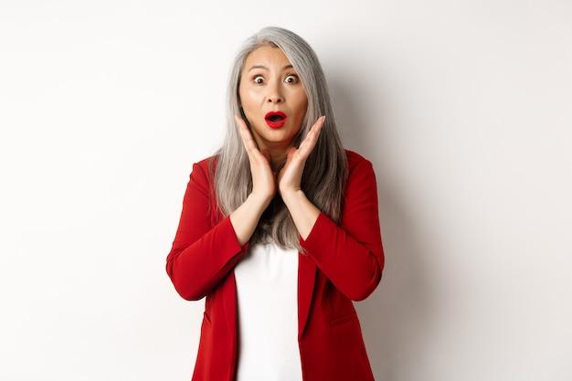 Uomini d'affari. asian senior imprenditrice in giacca rossa e trucco senza fiato, guardando sorpreso a porte chiuse, in piedi su sfondo bianco.