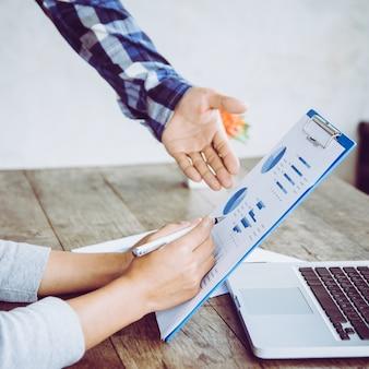 Gli uomini d'affari brainstorming alla scrivania, stanno analizzando i rapporti finanziari e indicando i dati finanziari su un foglio