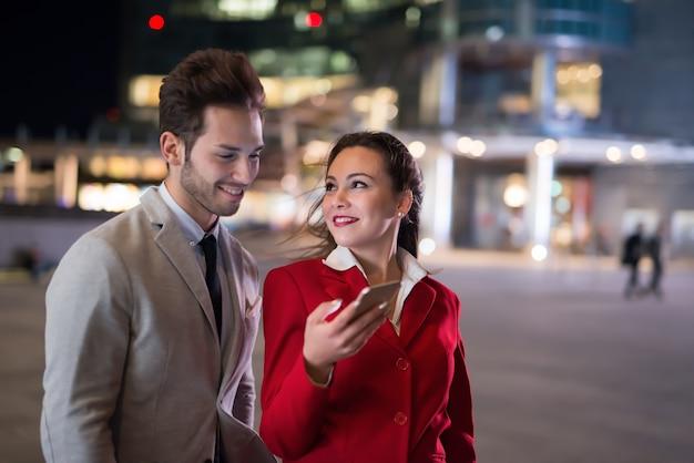 Uomini d'affari uomo d'affari e imprenditrice utilizzando uno smartphone di notte in una città