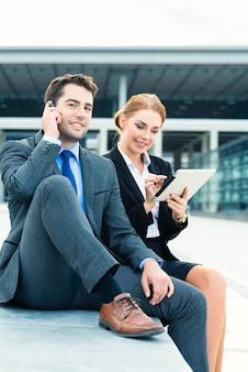 Uomini d'affari o uomo d'affari e donna d'affari che lavorano all'aperto, utilizzando computer pad o tablet e telefono cellulare