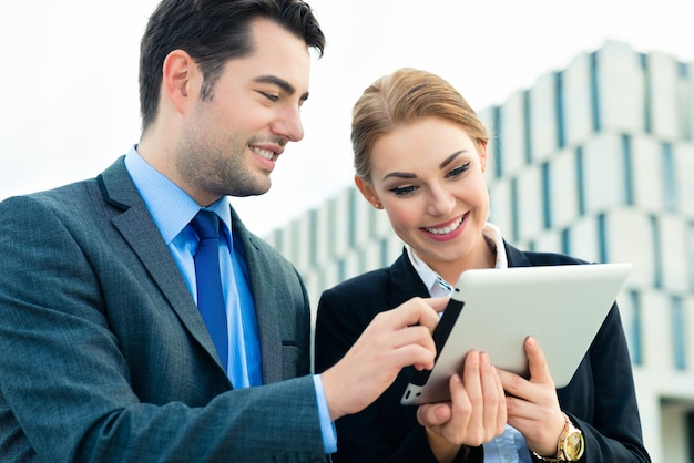 Uomini d'affari o uomo d'affari e donna d'affari che lavorano all'aperto, utilizzando computer pad o tablet