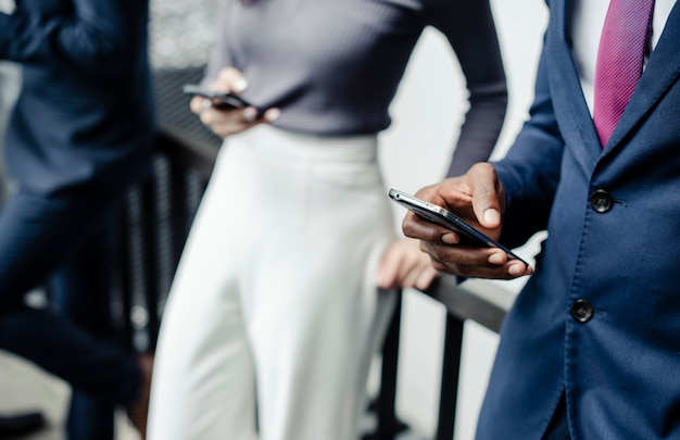 Uomini d'affari che usano casualmente gli smartphone all'aperto