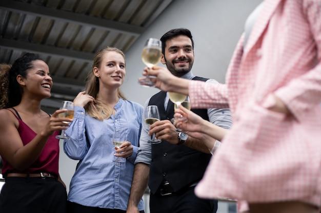 Gli uomini d'affari tintinnano bicchieri e bevono vino per celebrare il successo del lavoro. un gruppo di uomini d'affari festeggia bevendo vino con un sorriso.