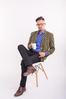 Concetto di persone e di affari - bell'uomo si siede sulla sedia e tiene una tazza su sfondo bianco.