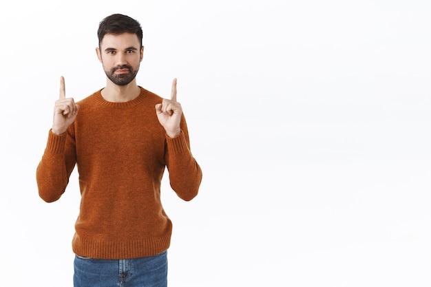 Affari, concetto di persone. ritratto di un bell'uomo barbuto sorridente che punta le dita verso l'alto, mostrando il modo per promuovere, consiglia il muro bianco del prodotto