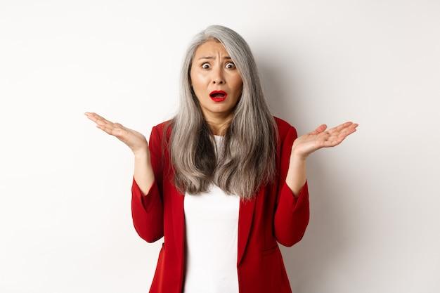 Uomini d'affari. confusa e ansiosa signora asiatica dell'ufficio senior che sembra preoccupata, allargò le mani lateralmente perplessa, in piedi su sfondo bianco.