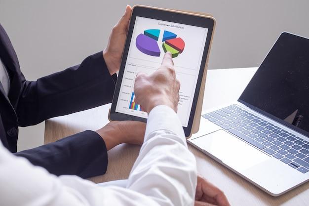 Gli uomini d'affari discutono di informazioni tramite tablet