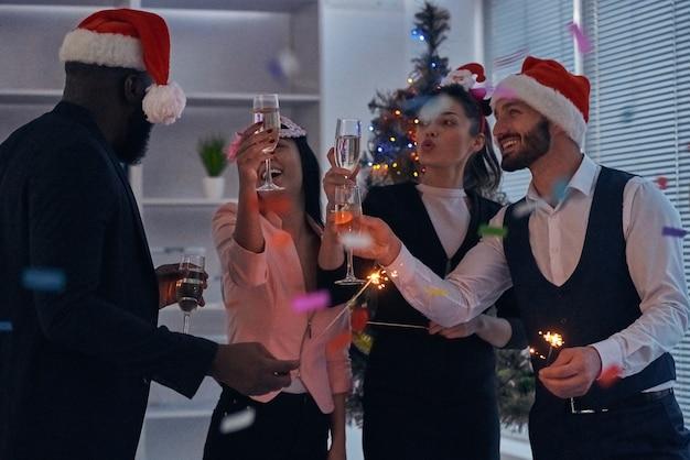 Gli uomini d'affari che bevono champagne sullo sfondo dell'albero di natale
