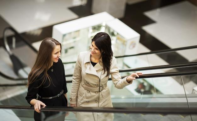 Uomini d'affari sulla scala mobile, due giovani imprenditrici a parlare