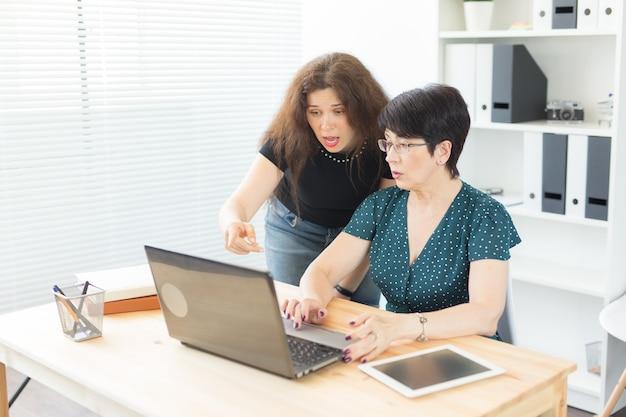 Uomini d'affari e concetto di graphic designer - le donne stanno discutendo idee in ufficio con il laptop