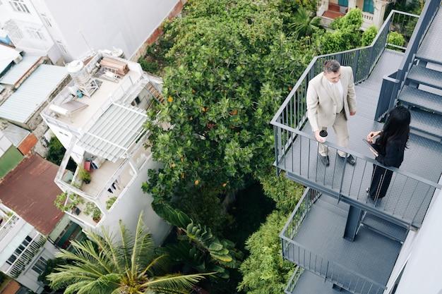 Gente di affari che ha una conversazione seria sulla scala antincendio dell'edificio per uffici, vista dall'alto